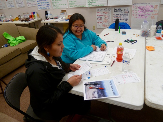 Two women at table reviewing Native language learning documents